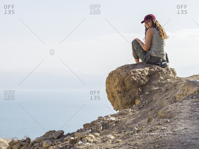 A Young Woman Sits On A Rock Looking Back And Posing For The Camera With A Cloud Covered Valley Down Below, Ein Gedi Nature Reserve, Dead Sea District; South Region, Israel