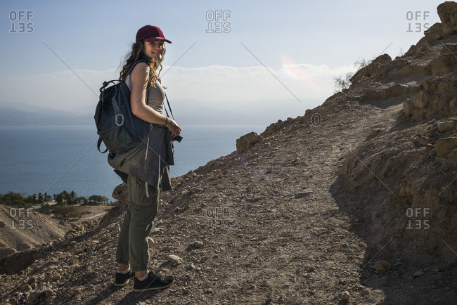 A Young Woman Poses While Hiking In Ein Gedi, With The Dead Sea In The Background, Dead Sea District; South District, Israel