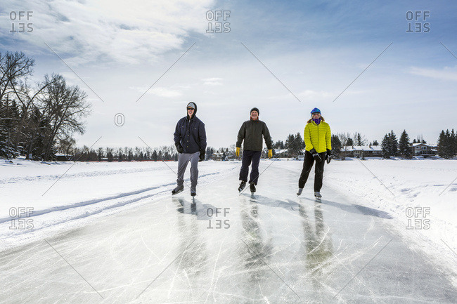 Two Males And One Female Skating On Freshly Groomed Ice On Pond With Houses In The Background; Calgary, Alberta, Canada