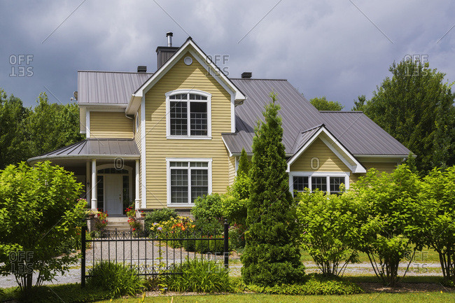 Yellow House With White Trim And Brown Metal Roof, Country Cottage Style Home Facade And Front Yard Garden Behind A Black Wrought Iron Fence In Summer; Quebec, Canada