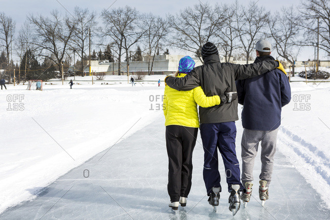 Two Males And One Female Skating Arm In Arm On Freshly Groomed Ice On Pond With Community Centre In The Background; Calgary, Alberta, Canada