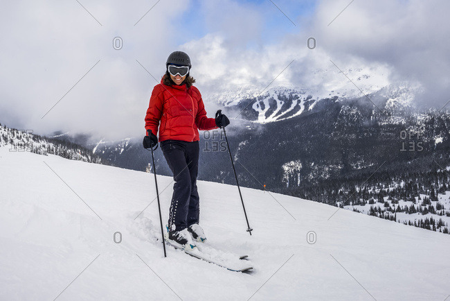 A Female Downhill Skier Poses For The Camera On A Ski Hill At A Ski Resort; Whistler, British Columbia, Canada