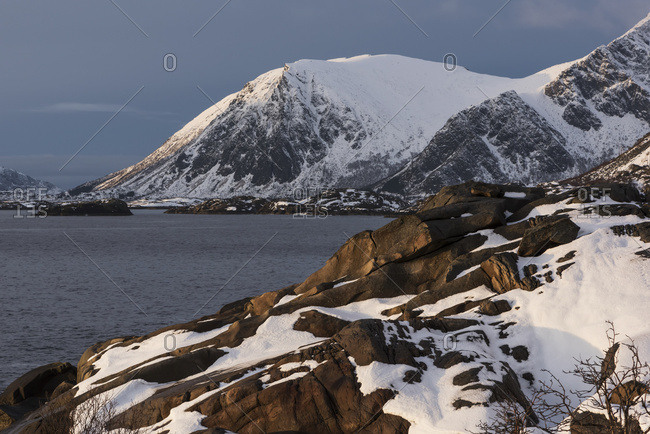 Rugged, Snow Covered Mountains Along The Coastline Of An Island; Lofoten Islands, Nordland, Norway