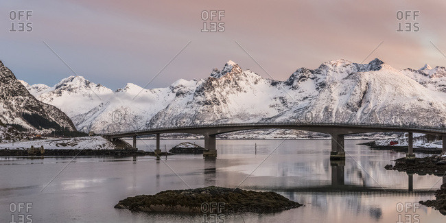 A Bridge Crossing The Tranquil Water With Pink Cloud Over The Rugged, Snow Covered Mountains; Nordland, Norway