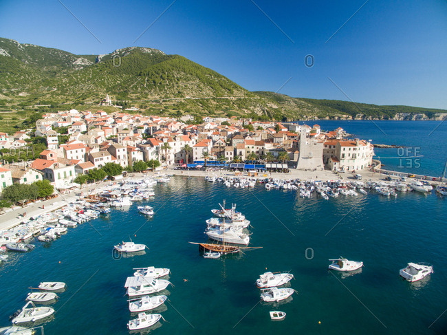 Aerial view of Komiza town and boats docked in marina on Vis Island, Croatia.