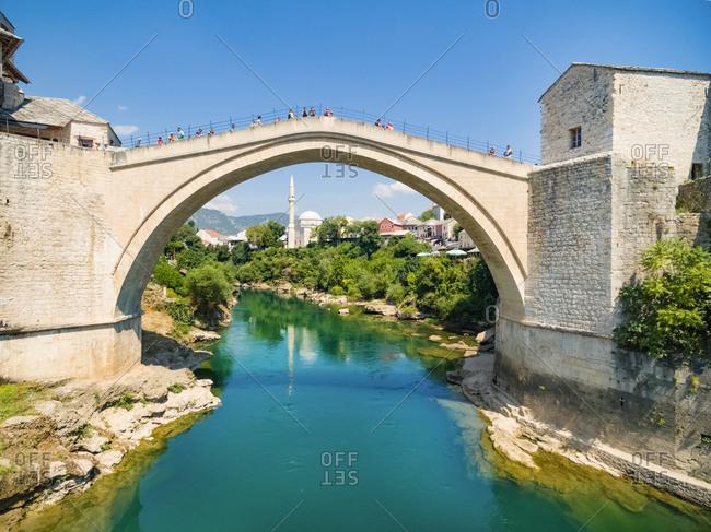 People crossing Old Bridge over Neretva river in Mostar, Bosnia and Herzegovina.