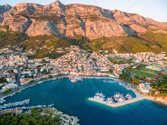 Aerial view on Makarska and marina at sunset with Biokovo mountain in background (Croatia).
