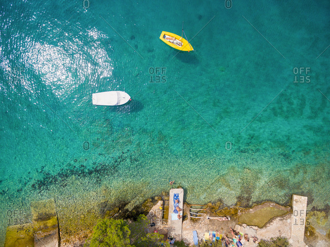 ADRIATIC COAST - SUMMER 2014: Aerial view of boat floating by the sea shore with people sun bathing.