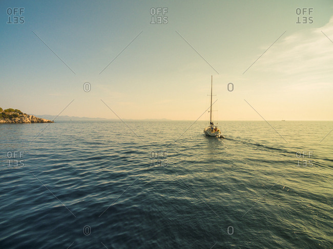 Aerial view of sailing boat going out to sea from bay.