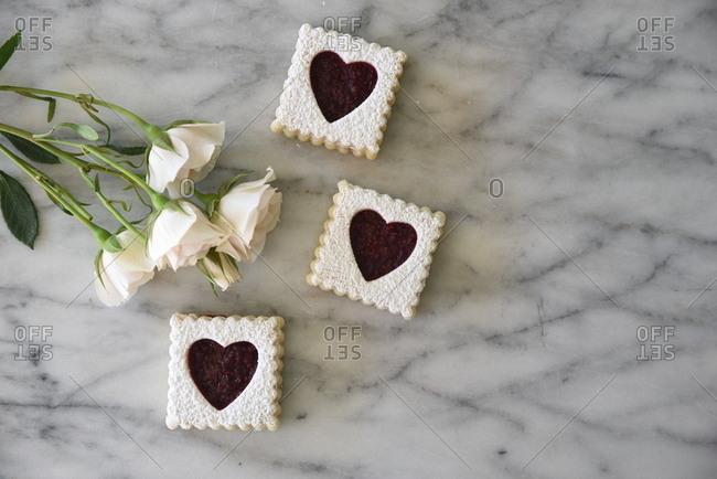Valentine cookies beside roses