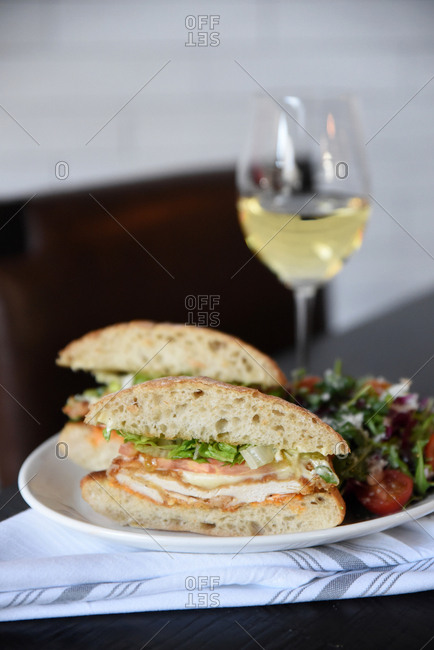 Sandwich and salad served with wine