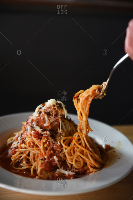Person eating spaghetti dish