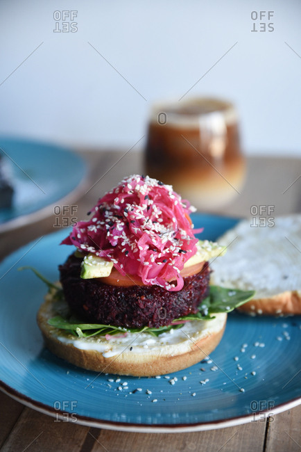 Veggie burger topped with pickled onions and sesame seeds