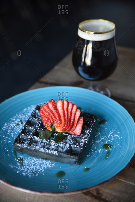Blue waffles topped with strawberries