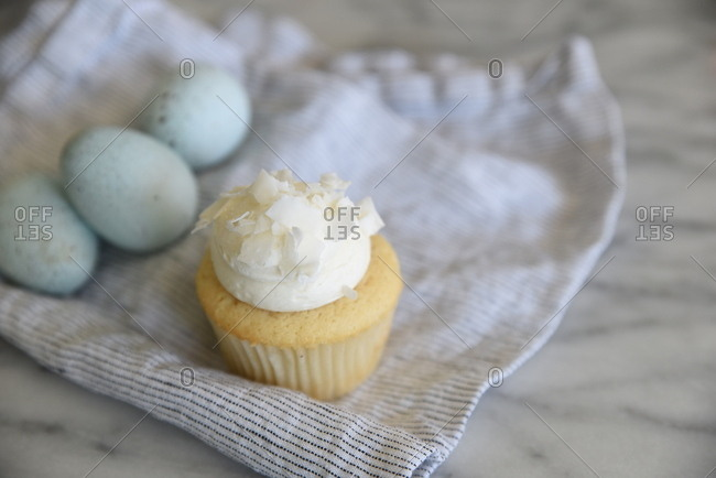 Small cupcake with white frosting and coconut flakes beside three eggs