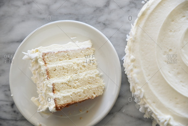 Slice of cake with white frosting and coconut flakes