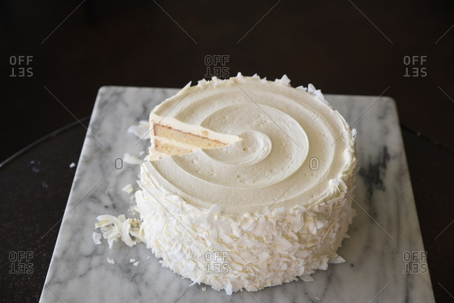 Cake with white frosting and coconut flakes missing a slice