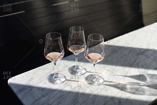 Three mostly empty glasses of blush wine
