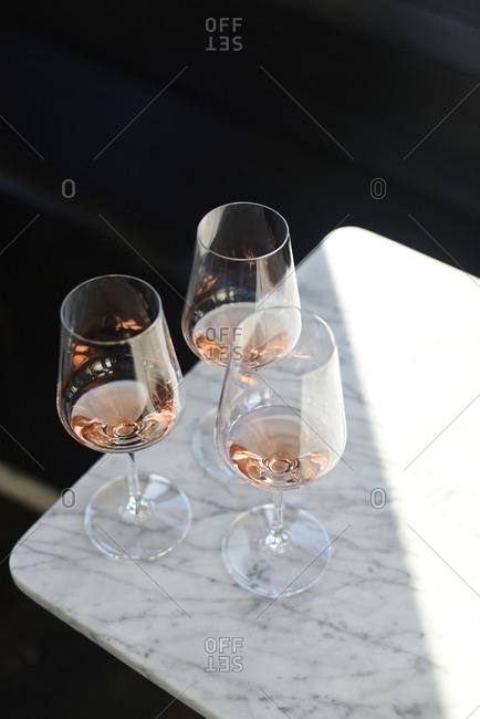 Three mostly empty glasses of wine