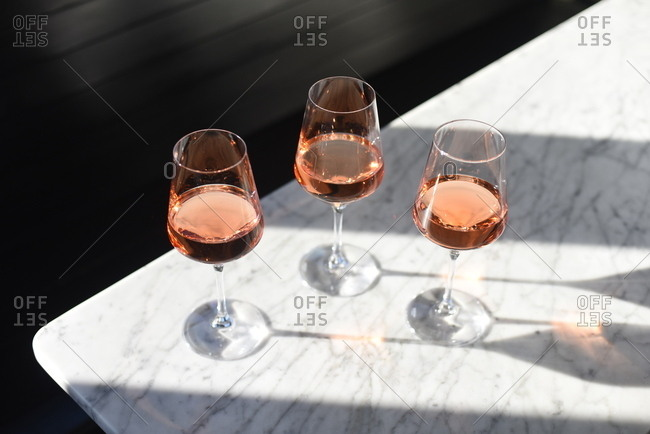 Three glasses filled with blush wine