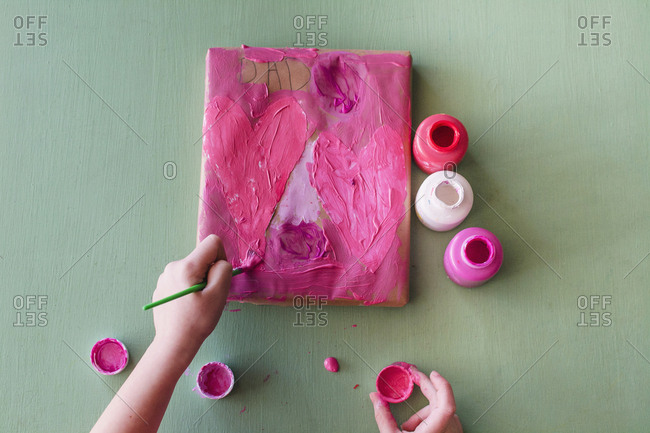 Young girl painting a valentine for Dad