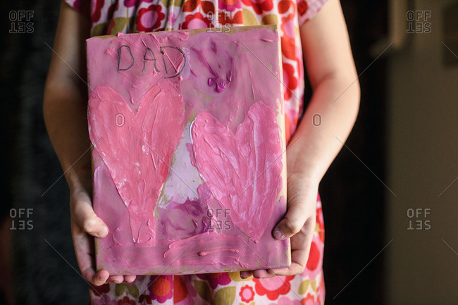 Young girl holding a valentine for Dad