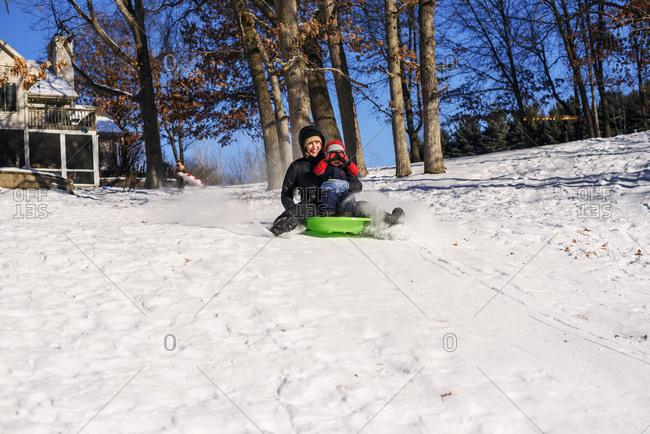 Mother and toddler sledding together