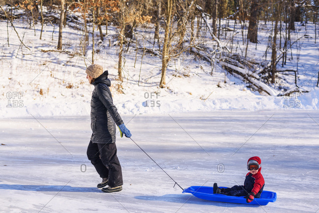 Mother pulling toddler on a sled