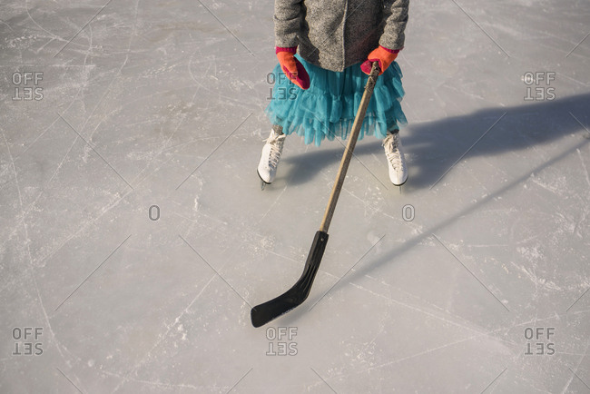 High angle view of young girl practicing ice hockey