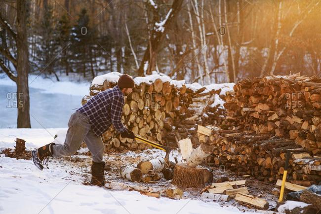 Man chopping wood at sunset