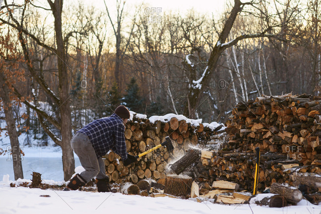 Man splitting wood at sunset