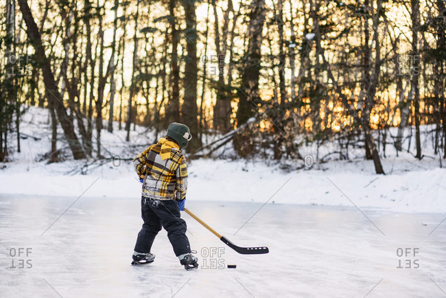 Young boy practicing ice hockey at sunset