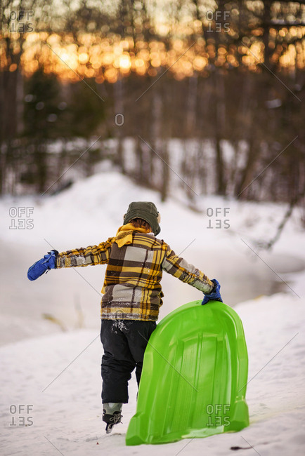 Young boy walking with sled on ice skates