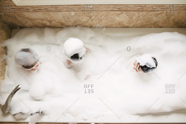 Overhead view of three kids playing in a bubble bath