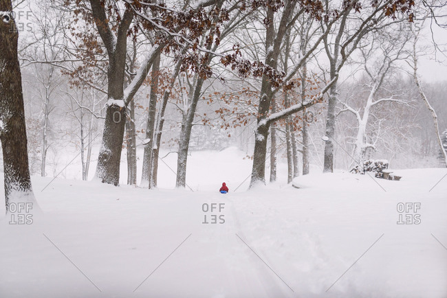 Young boy sledding in the heavy snow
