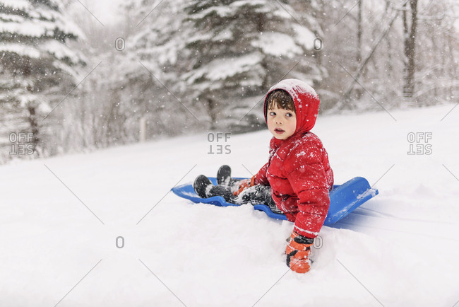 Young boy sledding on blue sled in the heavy snow