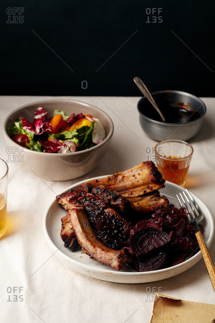 Main dish with grilled pork ribs in thick barbeque sauce garnished with red cabbage and beets braised in red wine sauce, fresh salad and crisp bread with sesame seeds