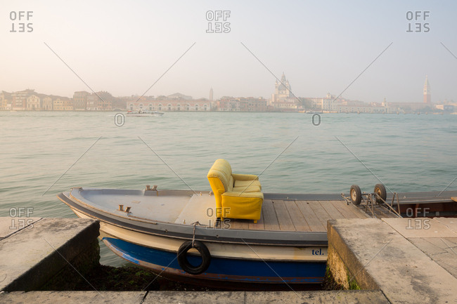 Yellow Sofa on a Boat in the Mist with Venice Skyline in the Background