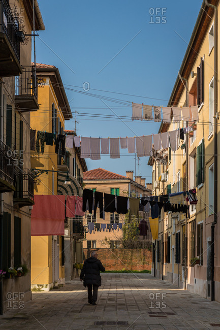 March 20, 2014: Person Walking Through the Small Alleys of the Giudecca Island in Venice