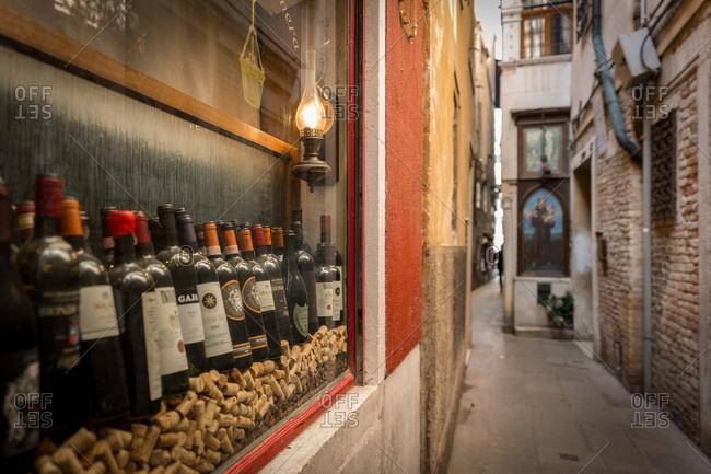 March 20, 2014: Bottles of Wine in a Shop Window in a small Venetian Alley