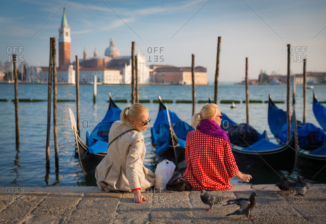 March 20, 2014: Two Blonde Girls on Venice Seafront Facing the San Giorgio Basilica and the Gondolas Floating on the Water in the San Marco Square Harbor