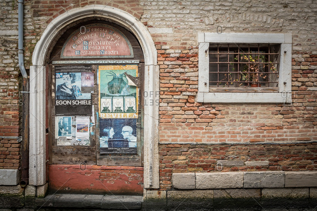 March 22, 2014: Old Wooden Door Covered in Posters and Barred Window Facing a Canal in Venice