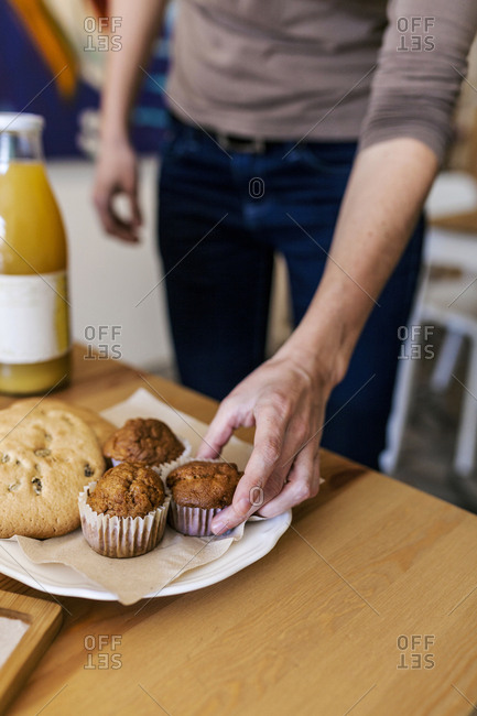 Person grabbing muffin from a plate