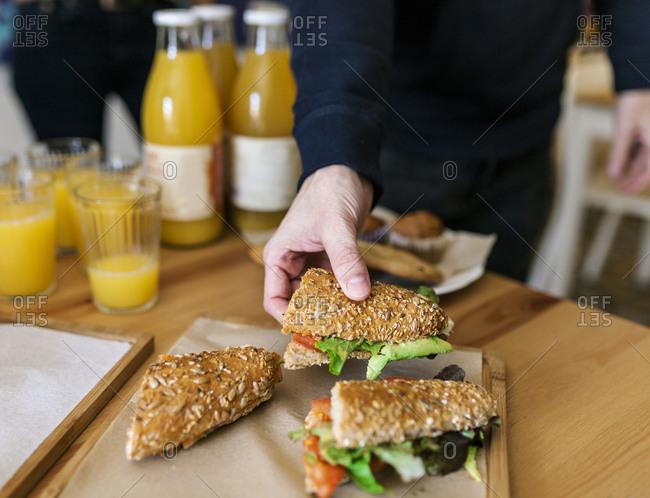 Man grabbing a sandwich