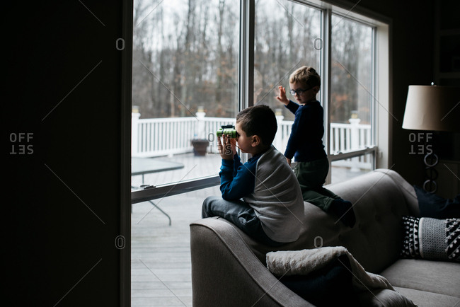 Two boys sitting on back of sofa looking out window with binoculars