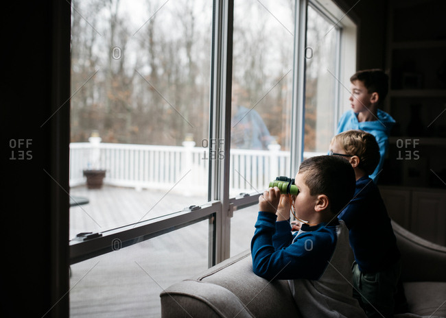 Three boys sitting on back of sofa looking out window with binoculars