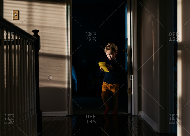 Young boy walking through doorway while playing with toy