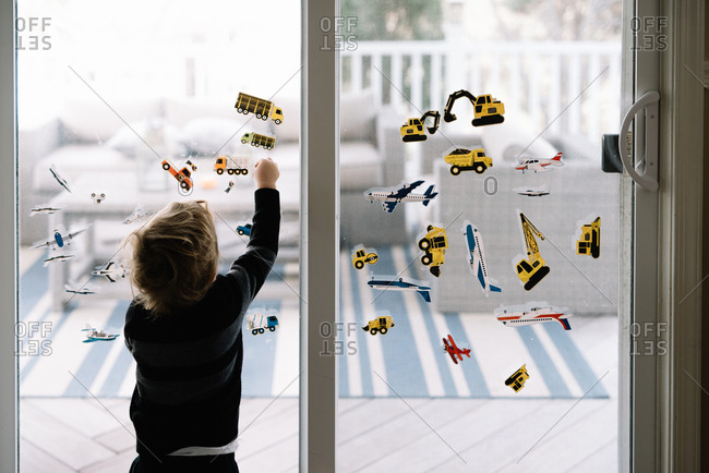 Rear view of boy placing stickers on sliding glass door