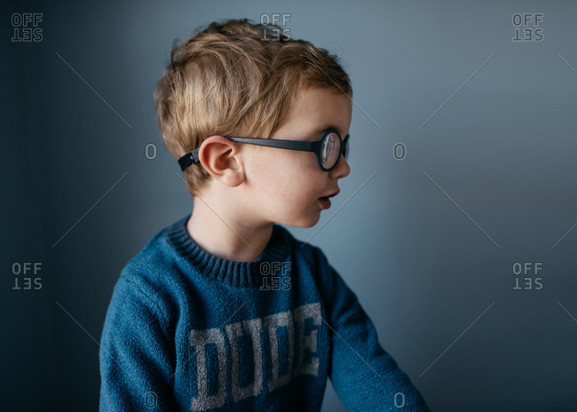 Portrait of a little boy with glasses looking away