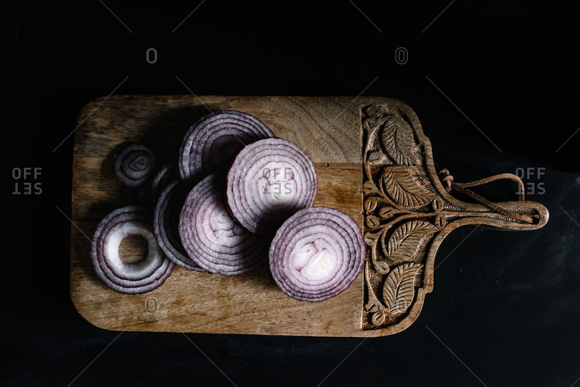 Sliced red onion on a wooden cutting board